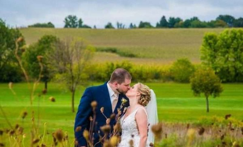 Complete Weddings Coordinator bridal couple kissing in field