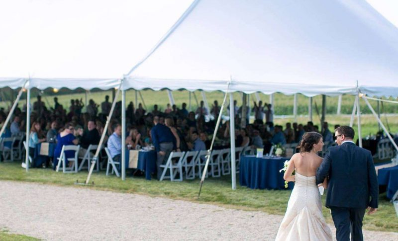 Bride and groom walk towards tent- Madison Party Rental