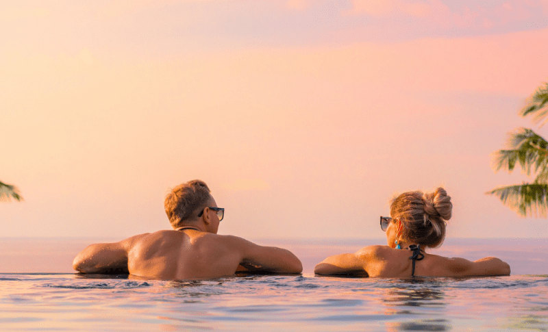 Couple at sunset in infinity pool overlooking ocean