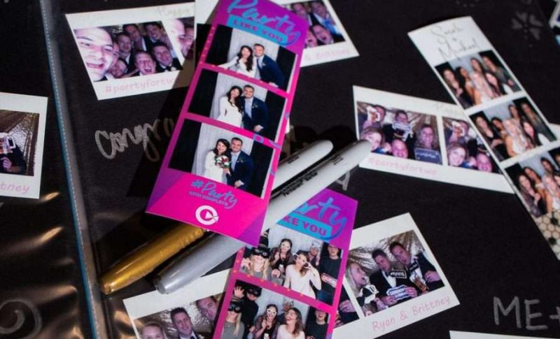 Fun guests at wedding reception using photo booth by Complete Weddings & Events