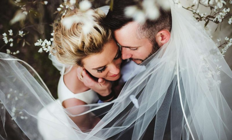 Intimate wedding couple with groom holding brides face by Twig and Olive Photography