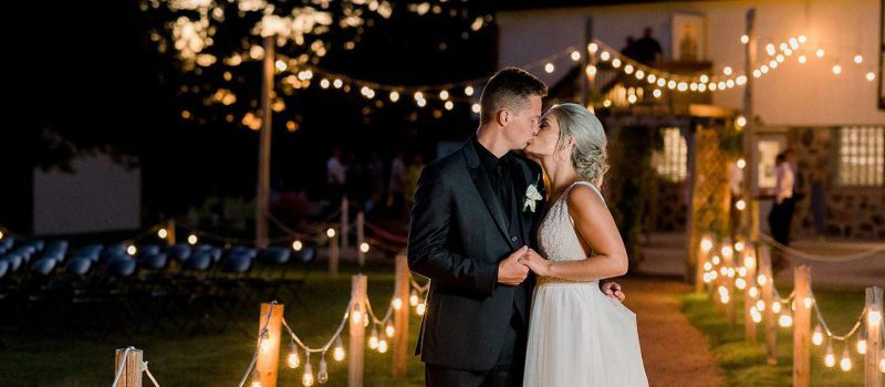Brittney and Rob kiss at dusk at The Hayloft